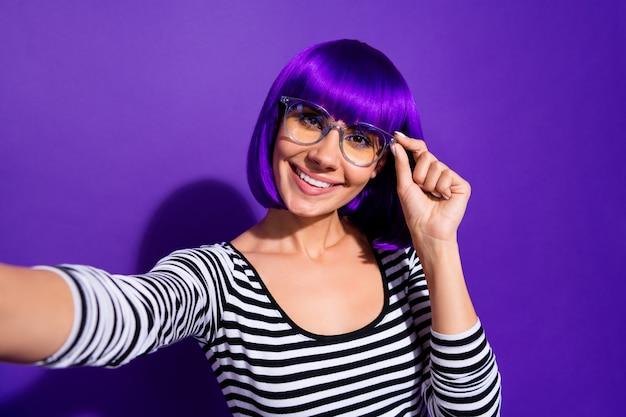 Close-up foto van vrolijke dame aanrakingsvlekjes maken foto glimlachend geïsoleerd over paars violette achtergrond