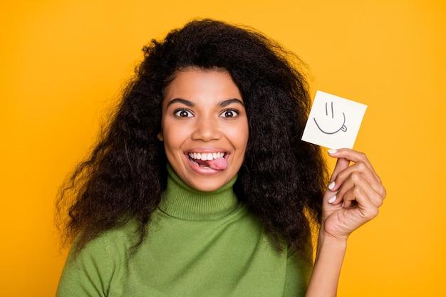 Close-up foto van vrolijke schattige mooie vrij positieve vriendin glimlachend toothily steekt tong uit met papier met haar emoji geïsoleerd levendige kleuren achtergrond