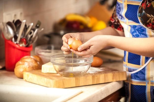 Close-up foto van vrouw brekend ei in glazen kom