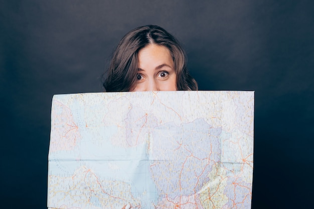 Close-up foto van vrouw die gezicht bedekt met wereldkaart Premium Foto
