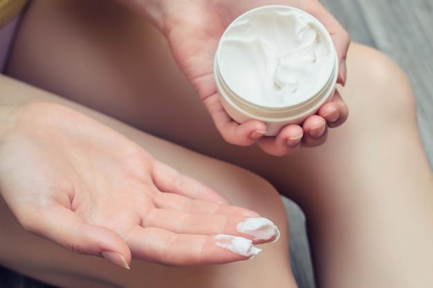 Close-up foto van vrouw die vochtinbrengende crème op haar lichaam aanbrengt