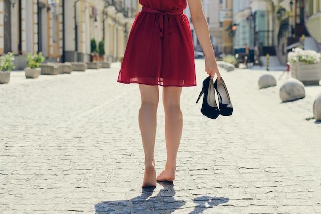 Close-up foto van vrouw in rode elegante jurk die haar schoenen met hoge hakken in handen houdt en blootsvoets loopt, uitzicht vanaf de achterkant, stad op de achtergrond