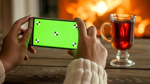 Close-up foto van vrouw met mobiele telefoon met groen chroma key-scherm op kamer ingericht voor kerstmis. perfect beeld voor vakantiereclame. plaats je eigen afbeelding