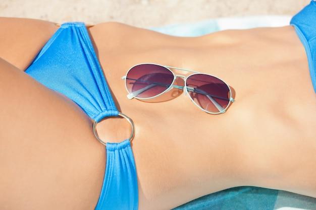 Close-up foto van vrouwelijke buik, bikini en tinten.