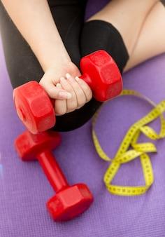Close-up foto van vrouwelijke hand tillen halter van fitness mat naast meetlint. concept van fitness en afvallen