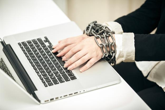 Close-up foto van vrouwelijke hand vastgeketend aan laptop