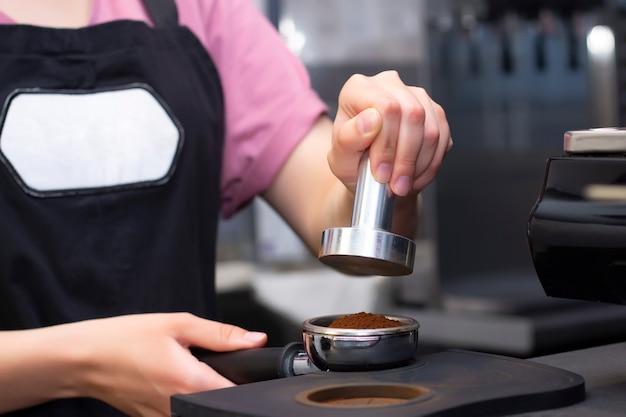 Close-up foto van vrouwelijke handen met een metalen stamper en een filterhouder met koffie in een coffeeshop. een barista die zich voorbereidt op het persen van gemalen koffie voor het brouwen van espresso of americano in een café