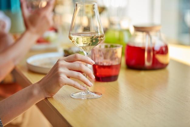 Close-up foto van vrouwelijke handen met glas champagne in restaurant