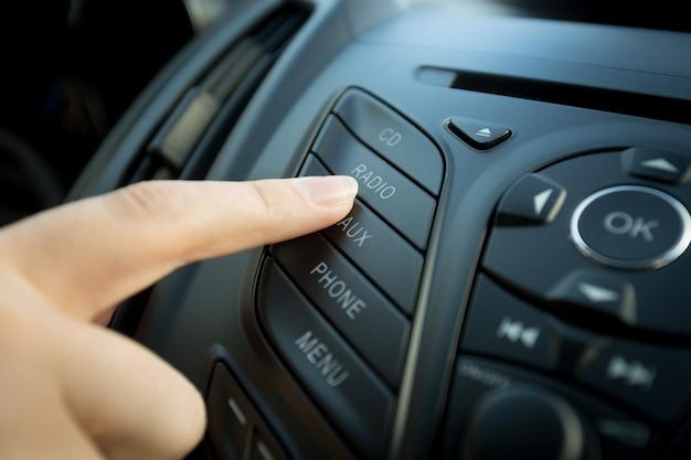 Close-up foto van vrouwelijke vinger die op de radioknop op het bedieningspaneel van de auto drukt