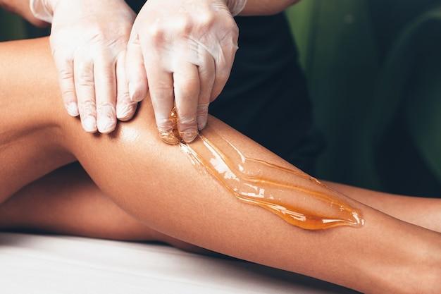 Close-up foto van waxing procedure op been in de moderne salon door een blanke schoonheidsspecialist