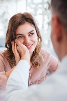 Close-up foto van zachte vrouw die op haar man kijkt en plezier neemt bij het houden van mannenhand op haar gezicht, terwijl ze een date heeft in een restaurant