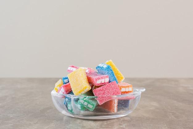 Close-up foto van zelfgemaakte kleurrijke snoepjes in kom over grijs.