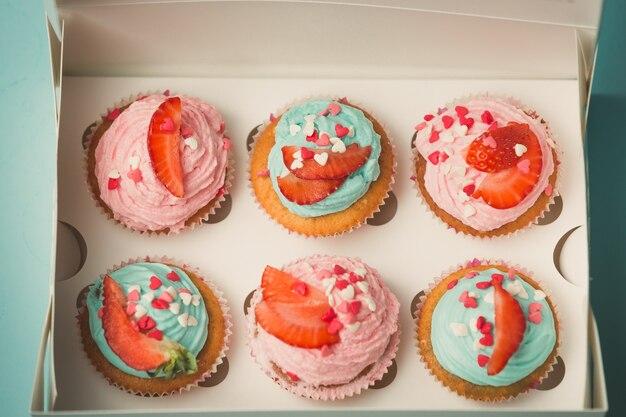 Close-up foto van zes versierde cupcakes in papieren geschenkdoos
