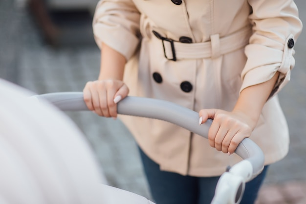 Close-up foto, vrouw handen met kinderwagen.