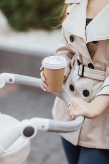 Close-up foto, vrouw met wegwerp koffiekopje en verblijf in de kinderwagen.