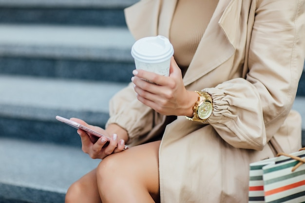 Close-up foto, vrouw na shoppig in de stad, boodschappentassen en koffietijd, telefoon vasthoudend, vrouw shopaholic.