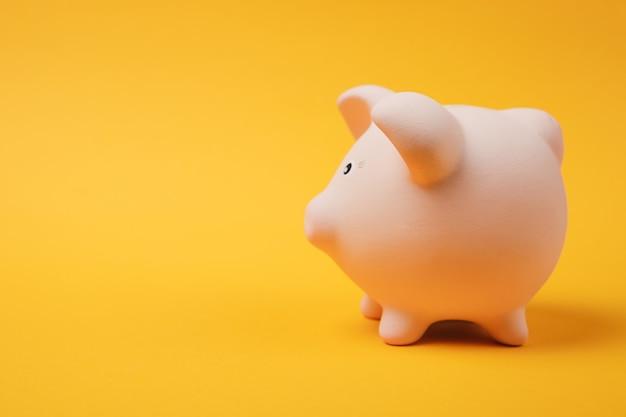 Close-up foto, zijaanzicht van roze spaarvarken geïsoleerd op felgele muur achtergrond. geld accumulatie investeringsbankieren of zakelijke diensten rijkdom concept. kopieer ruimte reclame mock-up.