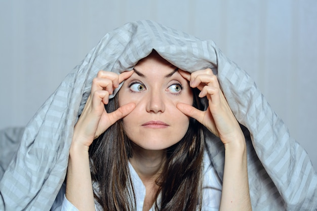 Close-up frontaal portret van een vrouw die haar ogen met haar handen houdt, die aan slapeloosheid lijden. angst, nachtmerries, gluren, je zien, kijken