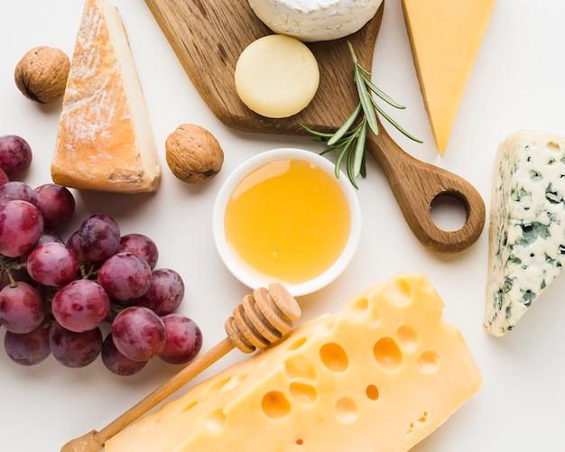 Close-up gastronomisch assortiment van kaas op houten snijplankhoning en druiven