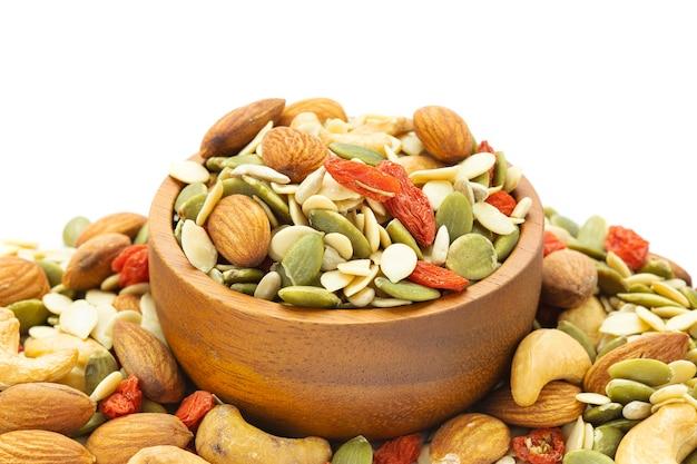 Close-up geassorteerde noten worden in een bruine houten beker op een wit oppervlak geplaatst met amandelen, zonnebloempitten, meloenzaden, cashewnoten, gekruide kee.