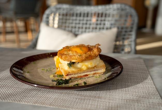 Close-up gebakken eiertop op ham en spinazie sandwiches op schotel voor het ontbijt op tafel in de ochtend
