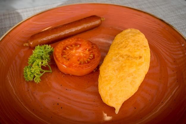 Close-up gebakken omelet met geroosterde worst en gesneden tomaat op schotel, zelfgemaakt ontbijt