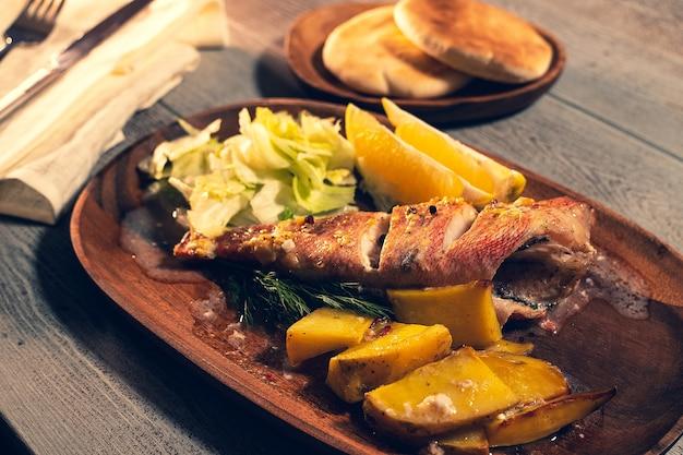 Close-up gebakken zeebaars. serveren op een houten schaal met gepofte aardappel en citroen. rustieke houten achtergrond.