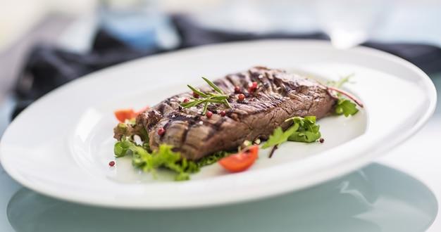 Close-up gedeelte van sappige flank steak van plantaardige salade zout peper en rozemarijn op witte plaat.
