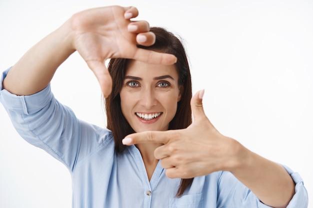 Close-up geïnspireerde vrouwelijke ondernemer van middelbare leeftijd legt eigen visie uit, maakt een foto, toont vingerframes en kijkt door de beeldopnamescène, staat op een witte muur geamuseerd glimlachend tevreden