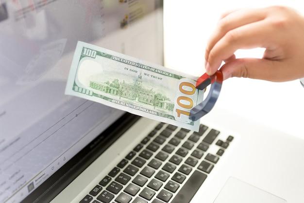 Close-up geïsoleerd geld van de mens die geld van laptop met magneet trekt