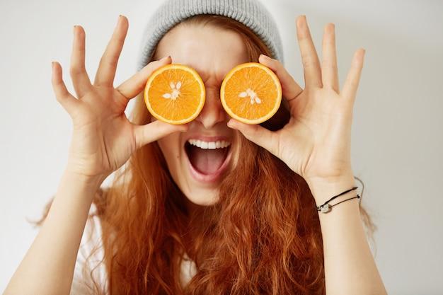 Close-up geïsoleerd portret van jonge roodharige vrouw met gehalveerde sinaasappels bij haar ogen