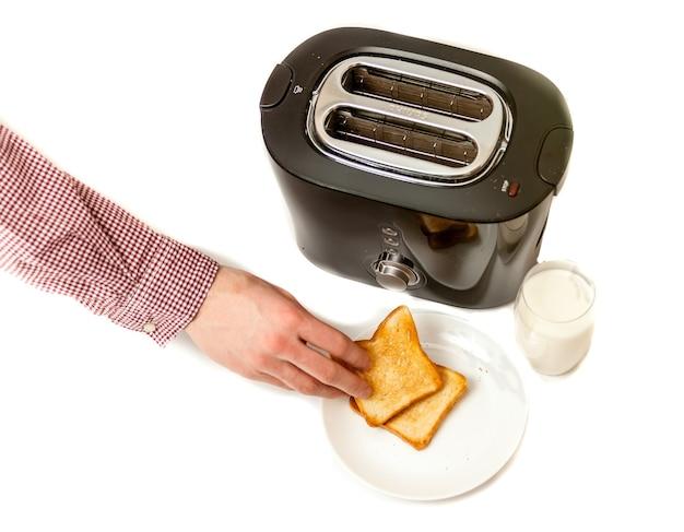 Close-up geïsoleerd schot van man die gebakken toast op witte schotel zet