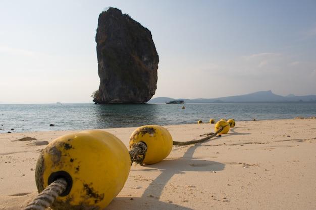 Close-up gele boeien met touw op het strand