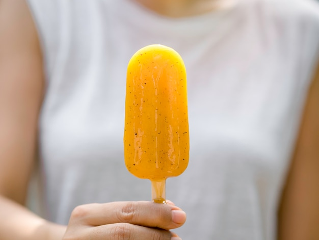 Close-up gele ijslolly in de hand van de vrouw met een casual wit mouwloos shirt, buitenshuis. vrouw die ijslollys eet. jonge vrouw genieten van ijs lolly in de zomer.