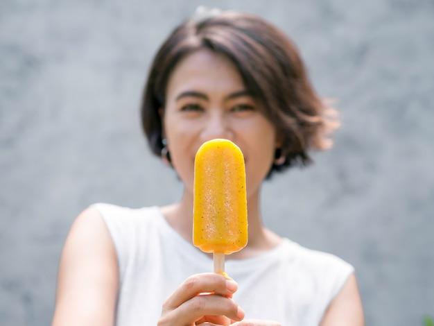 Close-up gele ijslolly in de hand van een mooie, gelukkige aziatische vrouw met een casual wit mouwloos shirt, buitenshuis. vrouw die ijslollys toont. glimlachend vrouwtje genieten van ijslolly in de zomer.