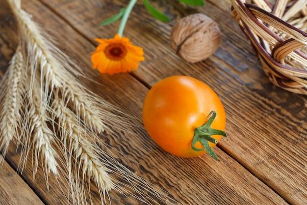 Close-up gele tomaat, walnoten, tarweoor, calendulabloem en rieten mand op oude houten planken. ondiepe scherptediepte. bovenaanzicht.