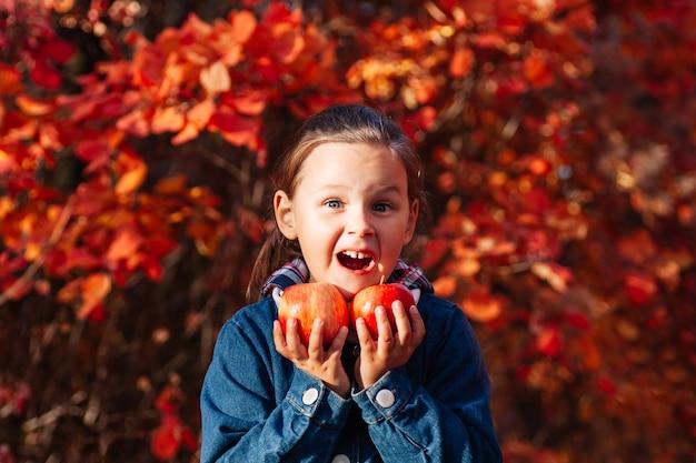 Close-up geluk concept schattig lachend meisje houdt grote rode appel met verrukking emotie op herfst backg...