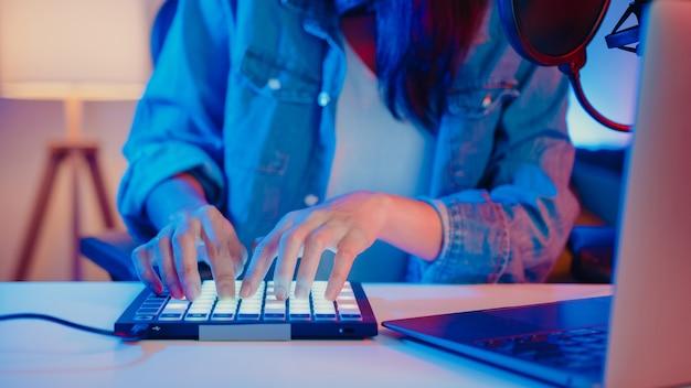 Close-up gelukkig aziatisch meisje dj met behulp van launchpad synthesizertoetsenbord