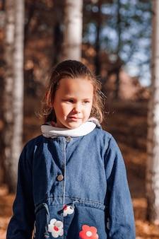 Close-up gelukkig kind concept schattig klein meisje in spijkerbroek jas met borduurbloemen in de herfst voor...
