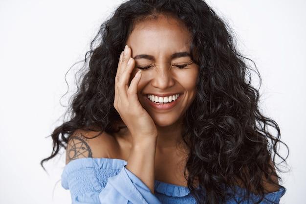 Close-up gelukkige, vrolijke en zorgeloze enthousiaste vrouw met tatoeage in stijlvolle, modieuze blauwe blouse, dichte ogen raken een heldere huid, lachen met plezier, staande witte muur
