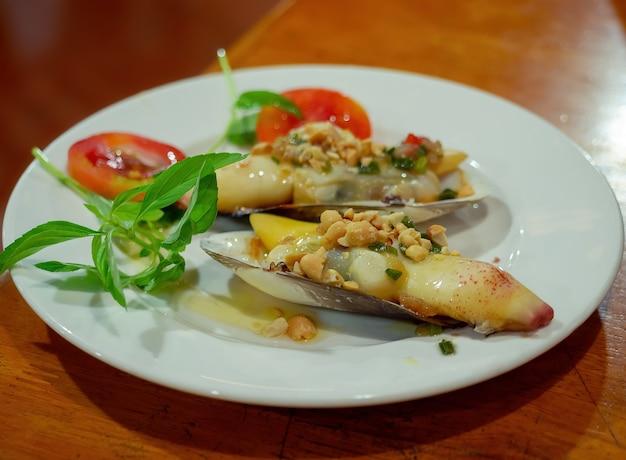 Close-up geoduck of olifant kofferbak clam gebakken met knoflook en kruiden in vietnam-stijl op schotel