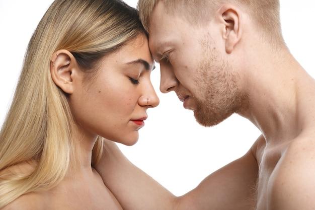 Close-up gepassioneerd paar ochtend samen doorbrengen: ongeschoren man houdt zijn blonde vrouwelijke minnaar met piercing in het gezicht bij haar nek. mensen, liefde, passie en seksualiteit concept