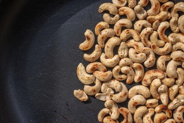 Close-up geroosterde cashewnoten en zout in een pan.