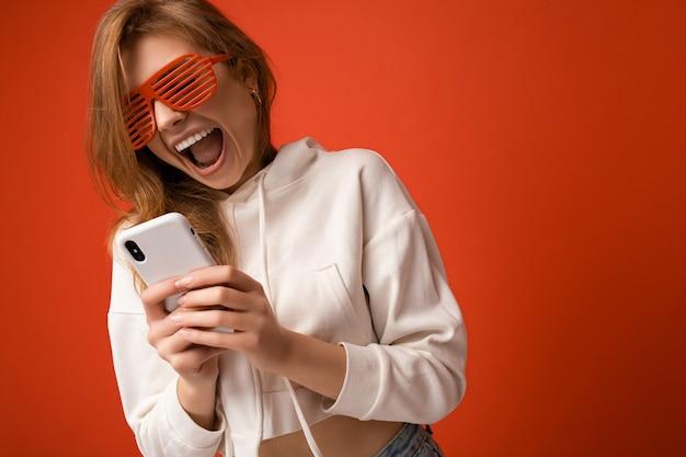Close-up geschokt emotionele jonge blonde vrouw, gekleed in een stijlvolle witte hoodie en grappig