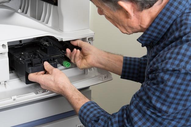 Close-up geschotene mannelijke technicus die digitale fotokopieerapparaatmachine herstellen