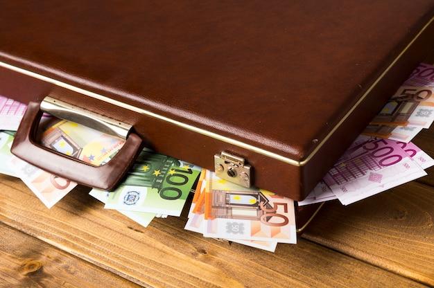 Close-up gesloten koffer met binnen bankbiljetten