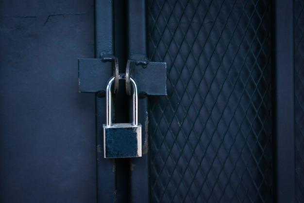 Close-up gesloten poort, hangslot op een metalen ijzeren poort.