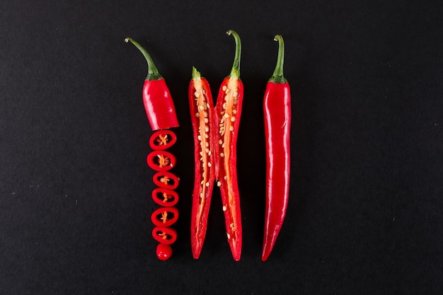Close-up gesneden rode chili peper op zwarte oppervlak geïsoleerd