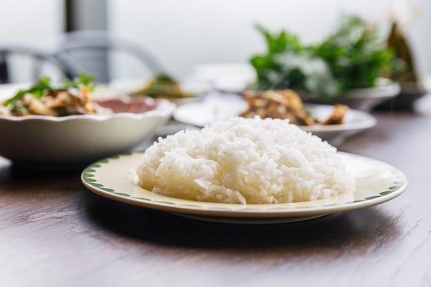 Close-up gestoomde rijst in een plaat die met de achtergrond van het onduidelijk beeldvoedsel wordt gediend.