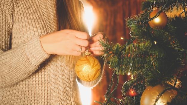 Close-up getinte afbeelding van een vrouw die naast een groot raam staat en de kerstboom versiert met kerstballen